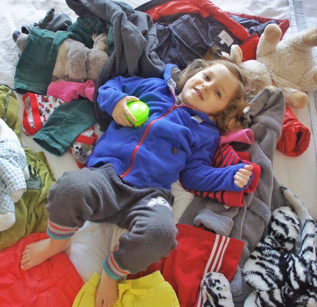 Miles Storm playing among a bunch of his outgrown clothes and toys